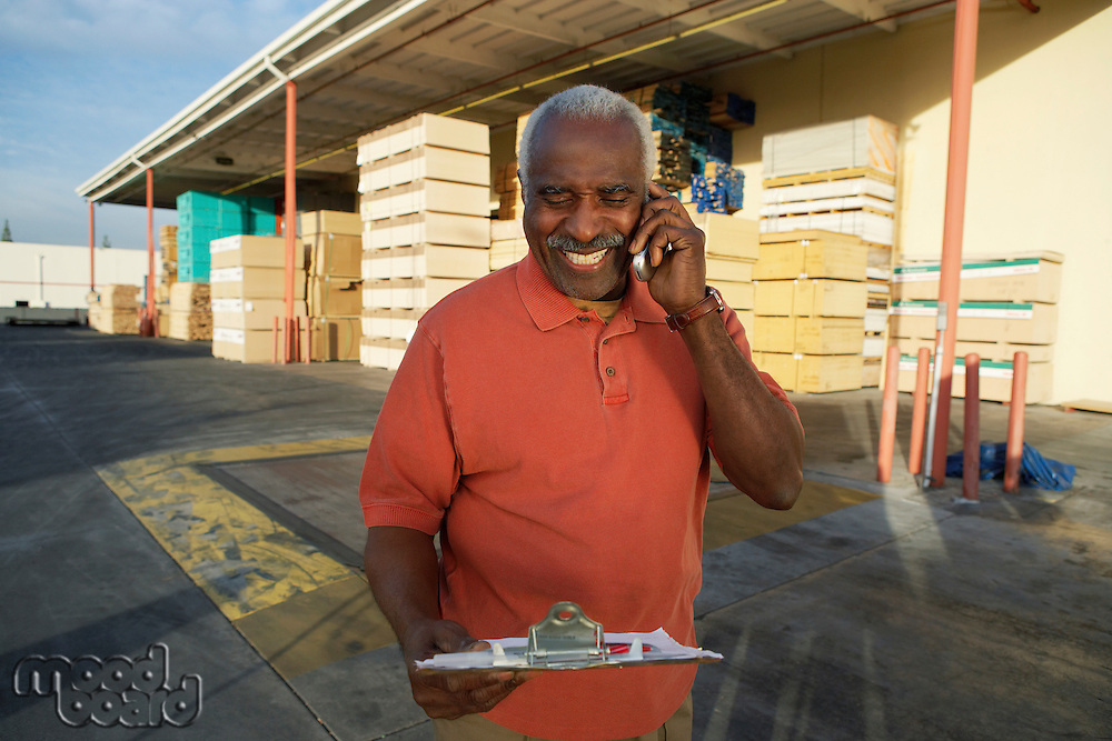 Manager on Cell Phone by Loading Dock of Lumber Warehouse