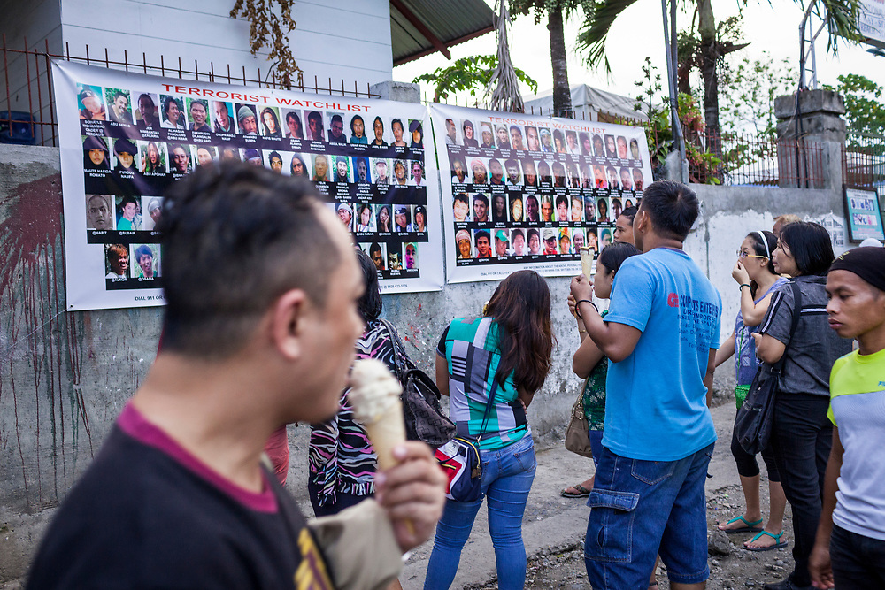Davao City, Mindanao, Philippines - JUNE 18: Visitors enjoying their ice cream examine two large posters of Wanted Terrorist posted at the Roxas Night Market.  Roxas Night Market was bombed on September 16, 2016.  14 people were killed and 70 were injured and three men who are linked to the Maute Group were arrested for the bombing.
