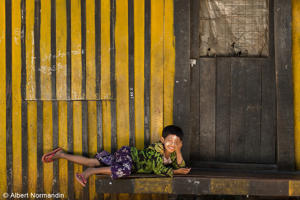 Boy laying down in front of striped wall, smiling, hiding one eye at Mogok entrance gate to Jade mining restricted region