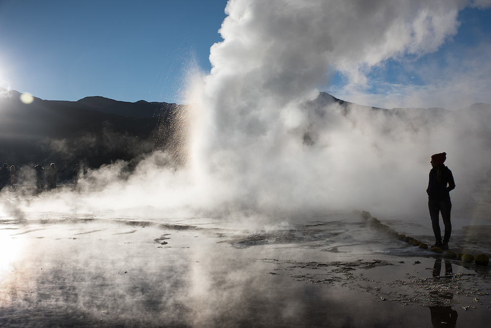 A woman watches the fumaroles of El Tatio at sunrise, Chile.