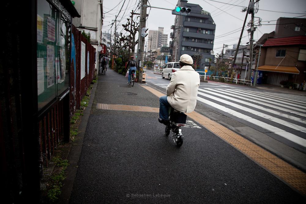TOKYO, JAPAN - 19 MARCH - Shinagawa  - a Man riding fastly a mini motor bike on the sidewalk. March 2012