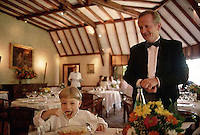 ca. September 1997, Saulieu, France --- Hubert Couilloud, maitre d'hotel at Bernard Loiseau's Cote d'Or restaurant, watches as a young boy eats. --- Image by © Owen Franken/CORBIS