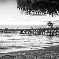 San Clemente CA black and white panorama photo with a straw tiki umbrella along the Southern California coastline. San Clemente is a popular coastal city in Orange County in the United States of America. Panoramic pphoto ratio is 1:3. Copyright ⓒ 2017 Paul Velgos with all rights reserved.