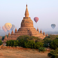 Hot air balloons fill the early morning haze on a flight over the temples, pagodas, and fields of Bagan by the Sitana Gyi Paya Pagoda.