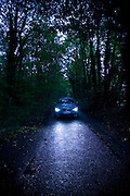BMW car on country road at nightfall, Gloucestershire, United Kingdom