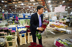 © London News Pictures. 21/05/2014. London, UK. ED MILIBAND, leader of The Labour Party buying a bunch of red roses for £10 during a visit to New Covent Garden Flower Market on the eve of the European election. Photo credit : Ben Cawthra/LNP