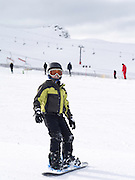A boy learns to snowboard at Cardrona Ski Area near Wanaka, New Zealand on a cold winter day; MR on file and available