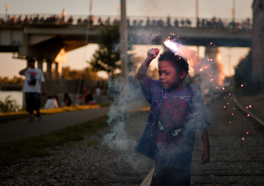 Marciano Young, 5, of Saginaw plays with a sparkler before a Fourth of July fireworks show in Saginaw.