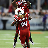 Louisville Cardinals quarterback Teddy Bridgewater (5) and defensive end Lorenzo Mauldin (94) celebrate a touchdown run during the NCAA Football Russell Athletic Bowl football game between the Louisville Cardinals and the Miami Hurricanes, at the Florida Citrus Bowl on Saturday, December 28, 2013 in Orlando, Florida. Louisville won the game by a score of 36-9. (AP Photo/Alex Menendez)