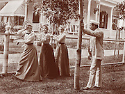 Vintage Photo: 3 flirtatious young women coyly posing at a fence as young man looks on appearing to be admiring or making a choice, circa 1900