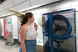 © Licensed to London News Pictures. 19/04/2018. London, UK. A woman cools down at a tube station using a giant fan as she walks to the platform. Today has been the hottest day of the year so far in the capital. Photo credit: Vickie Flores/LNP