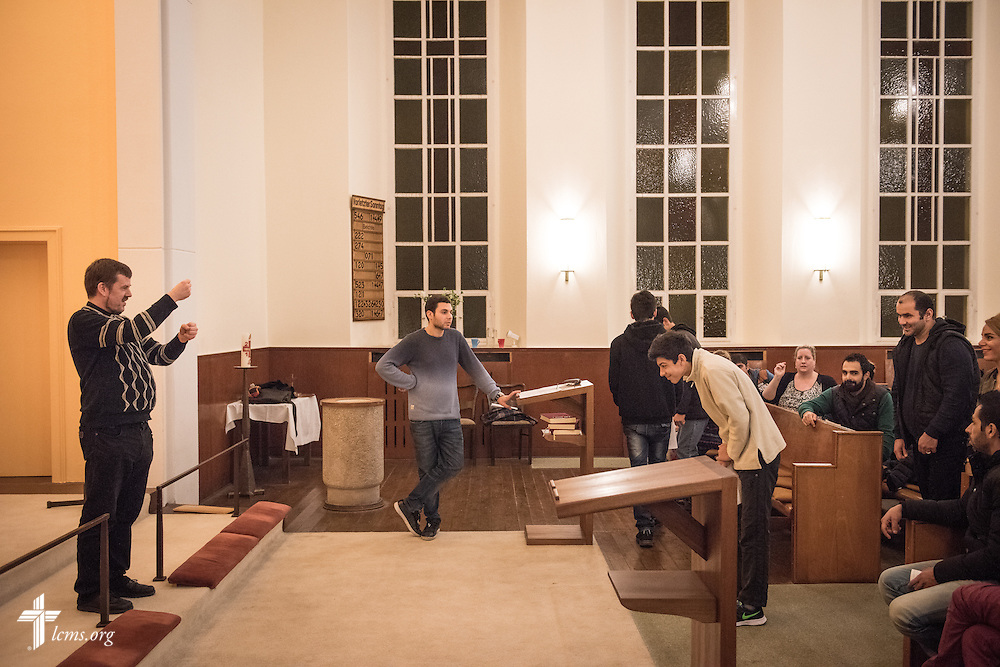 The Rev. Dr. Gottfried Martens runs through a baptism rehearsal on Saturday, Nov. 14, 2015, at the Dreieinigkeits-Gemeinde, a SELK Lutheran church in Berlin-Steglitz, Germany.  The refugees completed 3-months of intensive instruction before their baptism. LCMS Communications/Erik M. Lunsford