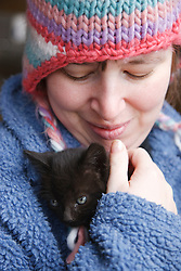Woman with learning disability holding kitten at farm