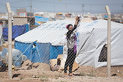 © Licensed to London News Pictures. 12/05/2013. Dohuk, Iraq. A Syrian refugee hangs washing on a fence inside the Domiz refugee camp in Iraqi-Kurdistan, set up for those escaping the ongoing civil war in Syria. The camp, close to the city of Dohuk, now houses in the region of 45,000 refugees, with around 400 new arrivals every day. Photo credit: Matt Cetti-Roberts/LNP