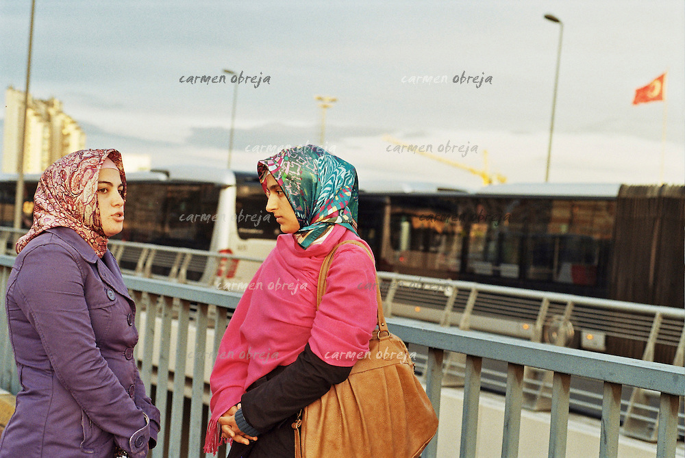two girls talking on a bridge in the levent area of istanbul