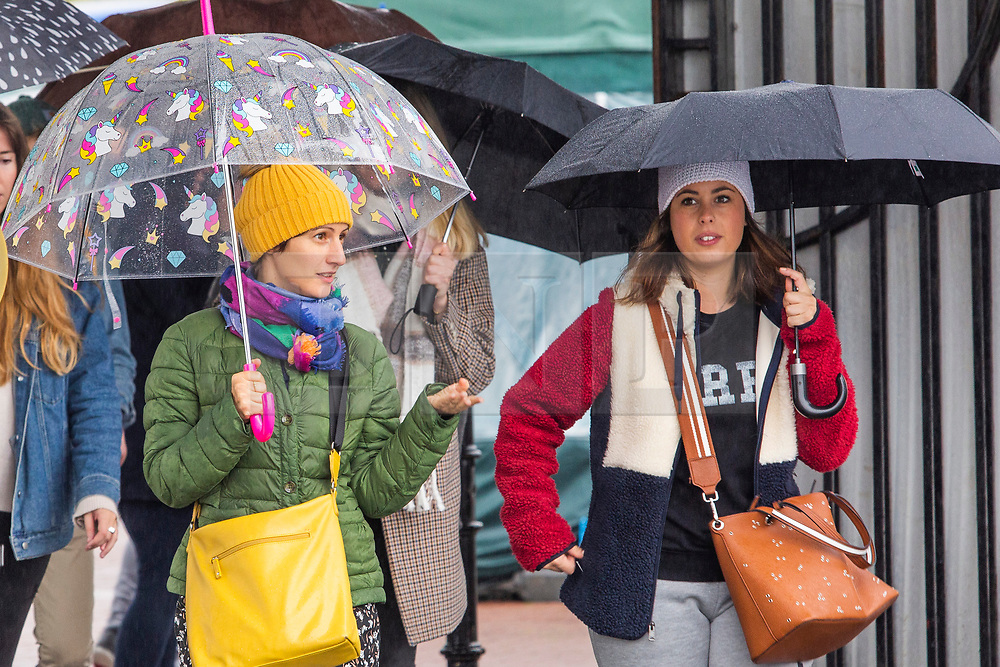 © Licensed to London News Pictures. 12/10/2019. Brighton, UK. Members of the public shelter from the rain in Brighton and Hove as wet and colder weather continues to hit the seaside resort. Photo credit: Hugo Michiels/LNP