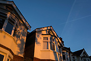 During the Coronavirus lockdown, a time when residents in the UK are asked to stay at home, semi-detatched period homes from the Edwardian era, are lit in evening sunlight with a rare commercial airliner passing overhead, leaving its vapour trail in a blue sky, on 20th May 2020, in London, England.