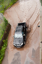 The same Nissan wheel drive leaves a wave like a boat as it moves through the deepest part of the flooding on Butterthwaite Lane Ecclesfield .28 June 2012.Image © Paul David Drabble
