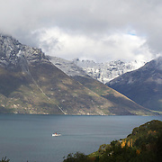 The TSS Earnslaw,  a 1912 Edwardian vintage twin screw steamer on the waters of Lake Wakatipu in, Queenstown, New Zealand. .It is one of the oldest tourist attractions in Central Otago, and the only remaining passenger-carrying coal-fired steamship in the southern hemisphere..The TSS Earnslaw heads along Lake Wakatipu from Queenstown  daily, running tourist trips to Walter Peak Station passing magnificent  peaks and contrasting shoreline foliage along the lakeside. Queenstown, New Zealand. 17th April 2011. Photo Tim Clayton