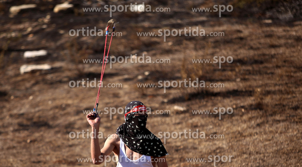 16.10.2015, Ramallah, PSE, Gewalt zwischen Pal&auml;stinensern und Israelis, im Bild Zusammenst&ouml;sse zwischen Pal&auml;stinensischen Demonstranten und Israelischen Sicherheitskr&auml;fte // A Palestinian protester hurls stones towards Israeli security forces during clashes near the Beit El settlement on the outskirts of Ramallah in the West Bank. The unrest that has engulfed Jerusalem and the occupied West Bank, the most serious in years, has claimed the lives of 34 Palestinians and seven Israelis. The tension has been triggered in part by Palestinians' anger over what they see as increased Jewish encroachment on Jerusalem's al-Aqsa mosque compound, Palestine on 2015/10/16. EXPA Pictures &copy; 2015, PhotoCredit: EXPA/ APAimages/ Shadi Hatem<br /> <br /> *****ATTENTION - for AUT, GER, SUI, ITA, POL, CRO, SRB only*****