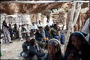 "Two young girls attend at their friends' early marriage celebration. Education is the most important key to helping end the practice of forced child marriages. Many believe that education may prove to be more successful in preventing child marriages than banning child marriages. North West of Ethiopia, on friday, Febrary 13 2009.....In a tangled mingling of tradition and culture, in the normal place of living, in a laid-back attitude. The background of Ethiopia's ""child brides"", a country which has the distinction of having highest percentage in the practice of early marriages despite having a law that establishes 18 years as minimum age to get married. Celebrations that last days, their minds clouded by girls cups of tella and the unknown for the future. White bridal veil frame their faces expressive of small defenseless creatures, who at the age ranging from three to twelve years shall be given to young brides men adults already...To protect the identities of the recorded subjects names and specific places are fictional."