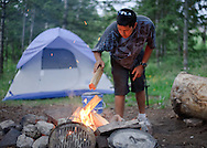 "Ruben Gonzales, 26, feeds the fire at a campsite in Curtis Canyon on Monday evening. The Spring Creek Ranch trail ride guide was born in Star Valley and grew up in both Star Valley and Arizona. ""I have places I could stay but I'd rather just be on my own,"" Gonzales said. ""I save a lot of money out here anyways, don't pay rent."""