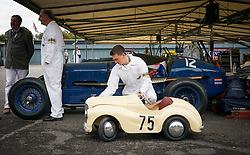 © Licensed to London News Pictures. <br /> 13/09/2019. <br /> Goodwood.West, Sussex. UK.<br /> The Goodwood Motor Circuit celebrates the 21st year of the Revival.This has become one of the biggest annual historic motorsport events in the world and the only one to be staged entirely in period dress. Each year over 150,000 people descend on this quiet corner of West Sussex to enjoy the three-day event.<br /> Pictured. A mechanic polishing an Austin J40 pedal car.<br /> <br /> <br /> Photo credit: Ian Whittaker/LNP