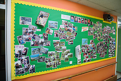 School notice board showing photos of students and activities,