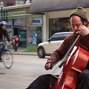 Street musician playing cello on University Avenue, Seattle, Washington