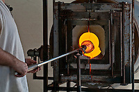 Glass artisan works with hot glass to create an artistic piece.