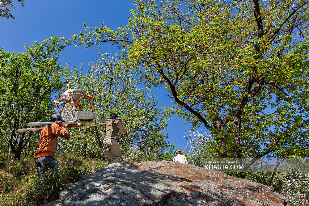 A Himalayan deity being carried in a palinquin through the apple orchards from Deori village to Kiari Village in Kotkhai region of Shimla, Himachal Pradesh, India