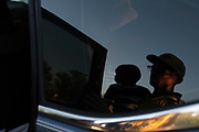 A reflection of Rev. Bojangle's holding his son Josiah is seen in his car window.