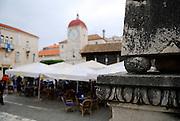 Detail of carved column base, with John Paul II Square (Trg Ivana Pavla II), Loggia and the Clock Tower of the church of St. Sebastian (sveti Sebastian) in background. Trogir, Croatia