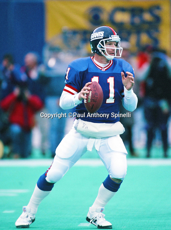 New York Giants quarterback Phil Simms (11) drops back to pass during the NFL football game against the Dallas Cowboys on Jan. 2, 1994 in East Rutherford, N.J. The Cowboys won the game in overtime 16-13. (©Paul Anthony Spinelli)