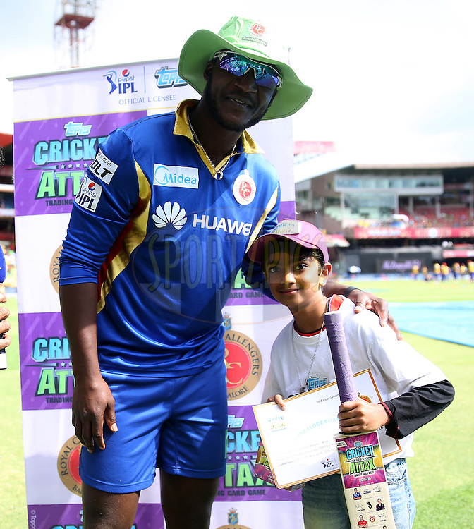 Royal Challengers Bangalore player Daren Sammy gives an award to Rushil Srirambhatla for the Bengaluru city champion bat of the Topps pepsi IPL cricket attax before the start of the match 55 of the Pepsi IPL 2015 (Indian Premier League) between The Royal Challengers Bangalore and The Delhi Daredevils held at the M. Chinnaswamy Stadium in Bengaluru, India on the 17th May 2015.<br /> <br /> Photo by:  Sandeep Shetty / SPORTZPICS / IPL
