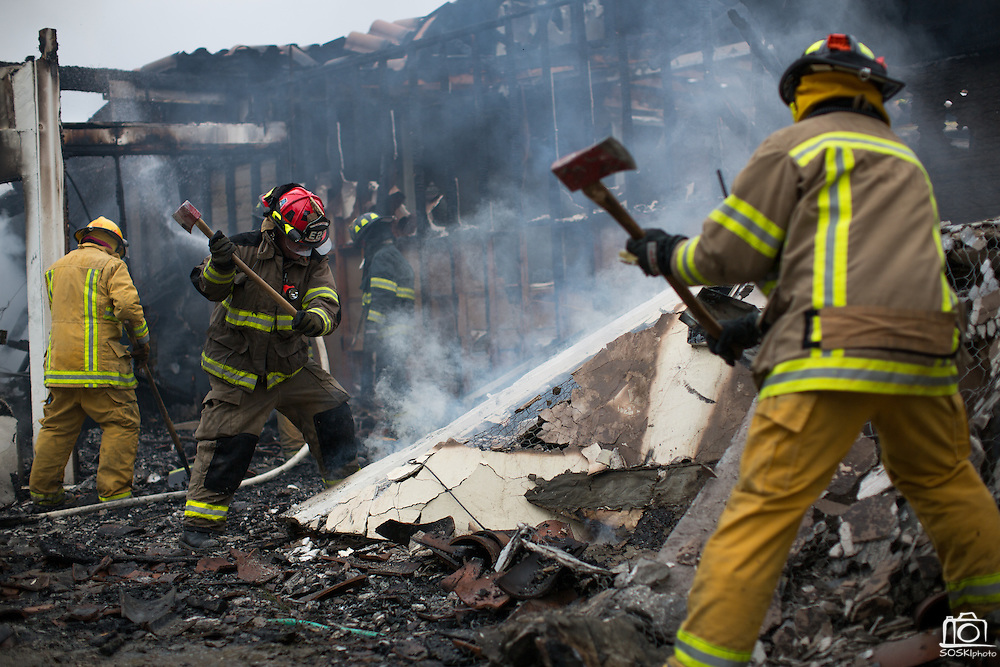Fire fighters break down walls as multiple fire departments, including Milpitas Fire Department, Spring Valley Fire Department, and Cal Fire, work to contain and extinguish a structure fire at the 3000 block of Calaveras Road near Spring Valley Golf Course in Milpitas, California, on February 10, 2014. (Stan Olszewski/SOSKIphoto)