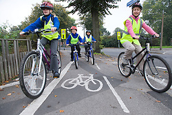 Children cycling home from school accompanied by a parent,