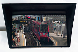 © Licensed to London News Pictures. 23/08/2012, London, UK.  Reflected in a platform mirror a DLR train leaves Poplar station in east London, Thursday, Aug. 23, 2012. DLR, Docklands Light Railway, is celebrates its 25th annivesary today. Photo credit : Sang Tan/LNP