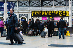 © Licensed to London News Pictures. 24/12/2013. London, UK. People wait for their trains at Paddington Rail station as they journey out of London for the Christmas break.  British Rail services are experiencing disruption as a result of adverse weather conditions. Photo credit : Richard Isaac/LNP
