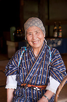 An elderly woman working at the Ryukyu Mura on the main island of Okinawa poses for the camera.