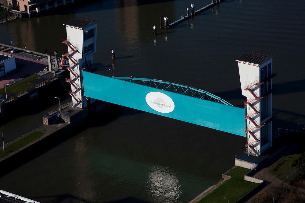 Nederland, Zuid-Holland, Capelle aan den IJssel, 20-03-2009; stormvloedkering in de Hollandsche IJssel. Bij storm en dreigend hoog water wordt een van de twee schuiven naar beneden gelaten, de tweede schuif dient al reserve. De scheepvaart kan de gesloten kering paseren via de naastgelegen schutsluis.   .De stormvloedkering maakt deel uit van de Deltawerken en is als eerste voltooid in 1958. Ten tijde van De Ramp - watersnood 1953 - werd het zeewater door de storm opgestuwd en dreigde de verzwakte rivierdijken in het achterland het te begeven waardoor grote van het laag gelegen westen van Nederland ondergelopen zouden zijn..Netherlands, Capelle at the river IJssel, near Rotterdam: storm surge barrier, protects the highly populated western part of Holland, which lies below sea level. In case of storm and threat of high water, one of the two doors is lowered into the river (the second door is a spare one). The lock next to the barrier allows shipping when the barrier is closed.Swart collectie, luchtfoto (toeslag); Swart Collection, aerial photo (additional fee required).foto Siebe Swart / photo Siebe Swart