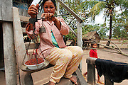 A women picker weighs a bowl of pepper on the steps of her house.