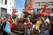 Women beating drumsticks and men wearing tall headdresses with paper flowers in the parade celebrating the festival of Ganesh Chaturthi, marking the birth of the Hindu god Ganesha, on the streets of the La Chapelle area of the 18th arrondissement of Paris, France, on Sunday 1st September 2019. The annual religious festivities and parade take place near the Ganesha Temple of Paris, or Sri Manicka Vinayakar Alayam Temple, the largest Hindu temple in France. Ganesha is the elephant-headed Hindu God of Beginnings, son of Shiva and Parvati, who represents love and knowledge. Picture by Manuel Cohen
