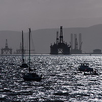 Oil rigs and small boats on Cromarty Firth. Platforms under repair.