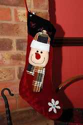 Father Christmas stocking as part of the Christmas decorations at home around the fire on Christmas morning indoors. Photo By i-Images