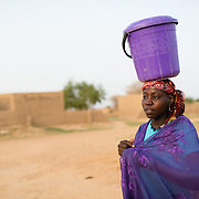 A woman carrying water home from a well refurbished by WaterAid in the village of Gadirga in the Commune of Soukoukoutan in the Dosso Region of Niger on 23 July 2013.