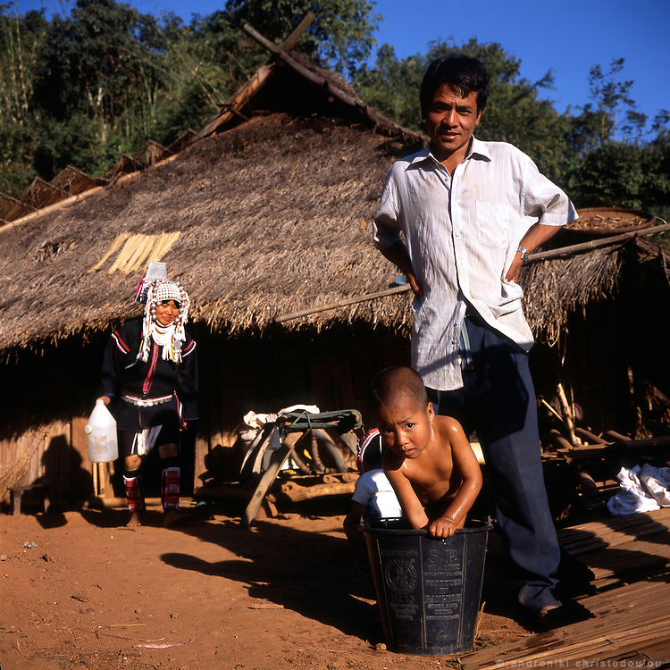 Akha family. Father giving his son a wash at the Akha village Huei Naam Kun that is located in the mountains near Chiang Rai.