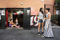 "ROME, ITALY - 3 JULY 2016: (R-L) Gipsy Queen Maria Miglescu (20) chats with volunteer Francesca, while other Gipsy Queen member Aninfa Hokic (31, left) laughs at the jokes of Grazia (12, daughter of Darmaz Florentina), during a break a break before heading to a food stand at the iFest, an alternative music festival, here at the entrance of the Astra 19 social center in Rome, Italy, on July 3rd 2016.<br /> <br /> The Gipsy Queens are a travelling catering business founded by Roma women in Rome.<br /> <br /> In 2015 Arci Solidarietà, an independent association for the promotion of social development, launched the ""Tavolo delle donne rom"" (Round table of Roma women) to both incentivise the process of integration of Roma in the city of Rome and to strengthen the Roma women's self-esteem in the context of a culture tied to patriarchal models. The ""Gipsy Queens"" project was founded by ten Roma women in July 2015 after an event organised together with Arci Solidarietà in the Candoni Roma camp in the Magliana, a neighbourhood in the South-West periphery of Rome, during which people were invited to dance and eat Roma cuisine. The goal of the Gipsy Queen travelling catering business is to support equal opportunities and female entrepreneurship among Roma women, who are often relegated to the roles of wives and mothers."