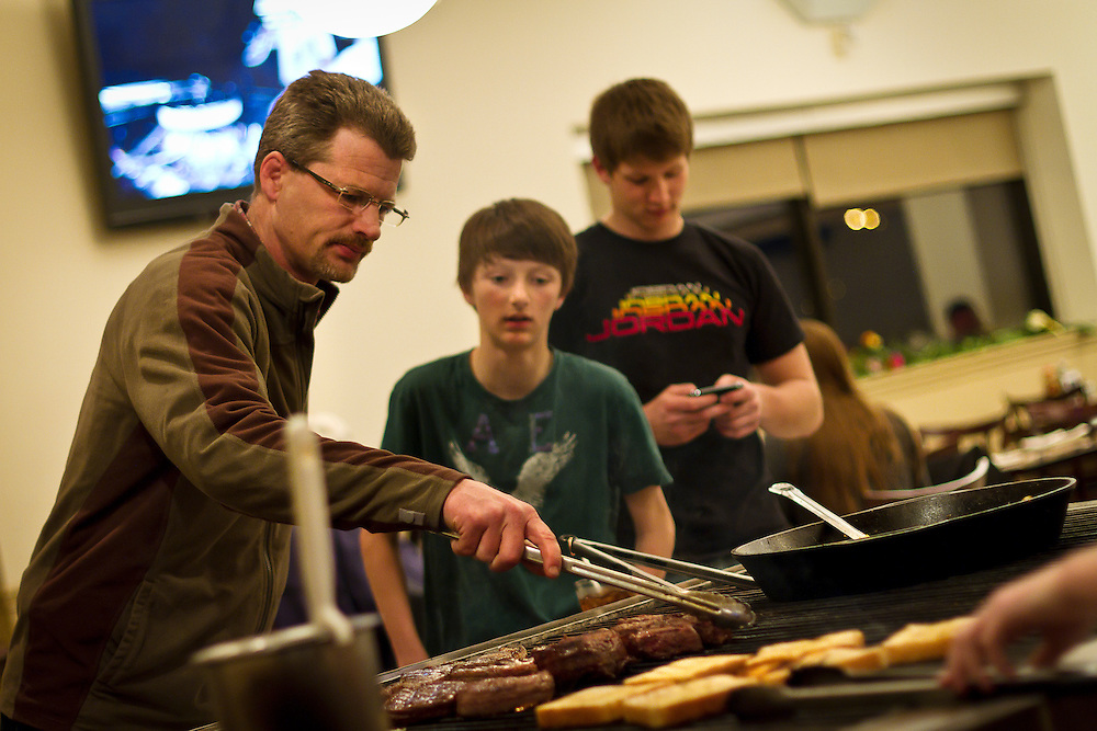 John Howerzyl, left, tends to a grill full of steaks for him and his two sons, Adam and Mason, at Grinnell Steakhouse on Thursday night..