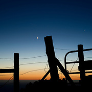 In Big Sur- silhouetted barbed wire fence and gate after sunset against dusk sky.